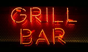 Neon inscription GRILL BAR in red on a dark wall. Neon text on the wall
